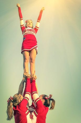 Cheerleader standing on other cheerleaders